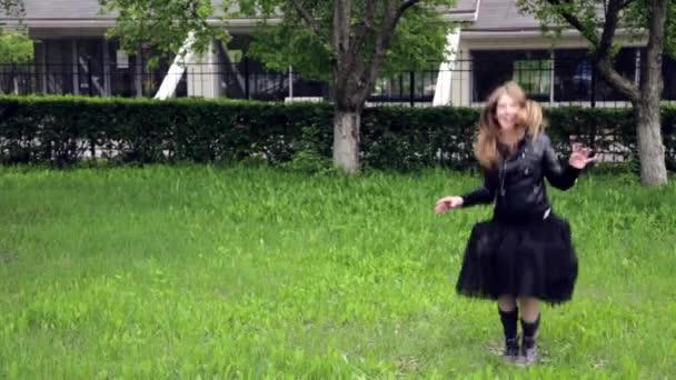 Dospívající dívka skákání a spinning crazy emoce v parku