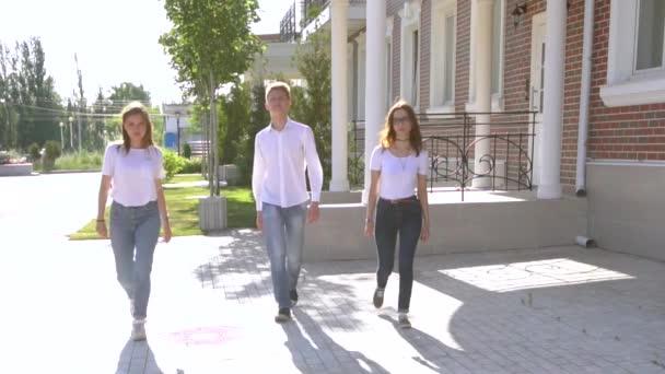 Tři dívky a chlapce na sobě podobných džíny a košile tančí na ulici