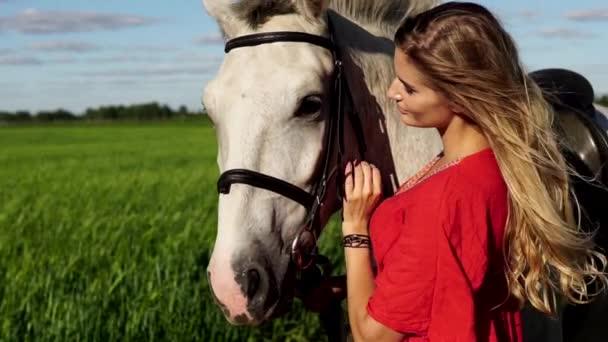 Portrét dreesed Mladá krásná žena v červené barvě s bílého koně v blízkosti pole