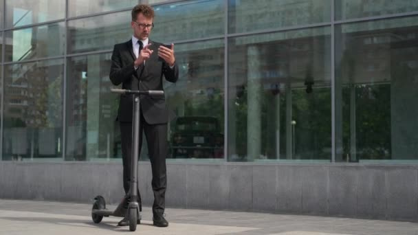 Man talking to colleague by video call on smartphone, electric scooter nearby