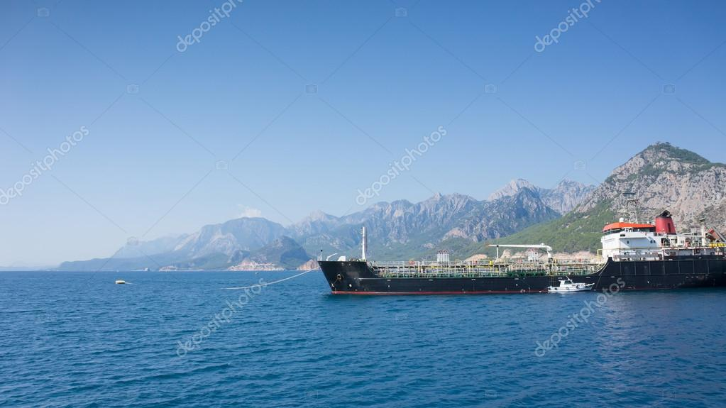 Big cargo ship in Mediterranean Sea, mountains on background