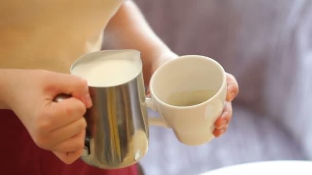 Nalití proud mléka, barista připraví latte v poháru
