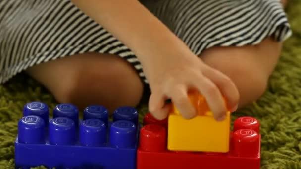 Roztomilá holčička hraje s bloky hračky, closeup