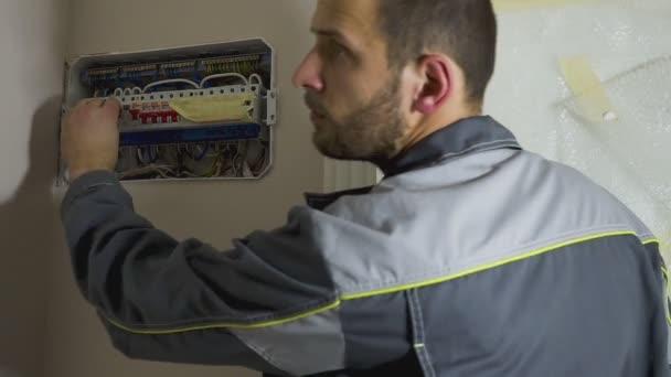 pohledný mladý muž elektrikář pracující na ústředně na domácí