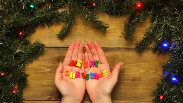 Ženy rozevírají ruce v rámečku se slovy Veselé Vánoce. Pohled shora, místo pro pozdravy