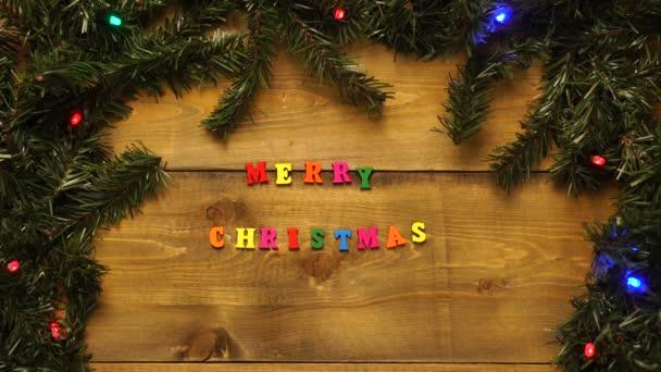 Vánoční dřevěný stůl je zdoben blikajícími věnci a barevným nápisem Veselé Vánoce.