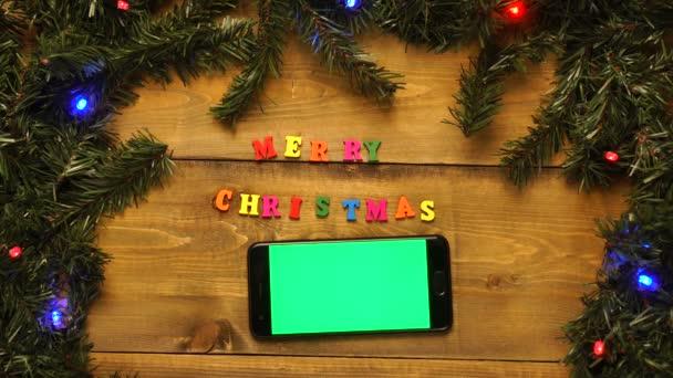 Telefon se zelenou obrazovkou a nápisem Veselé Vánoce na dřevěném stole s blikajícími věnci.