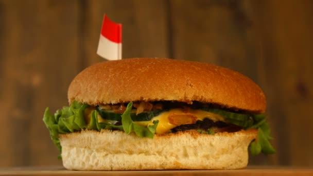 Köstliche Burger mit kleinen indonesischen oder Flagge auf ihnen mit Zahnstochern. Leckere Hamburger rotieren.