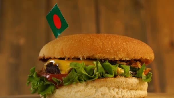 Köstlicher Burger mit einer kleinen Flagge Bangladeschs darauf mit Zahnstochern. Leckere Hamburger rotieren.