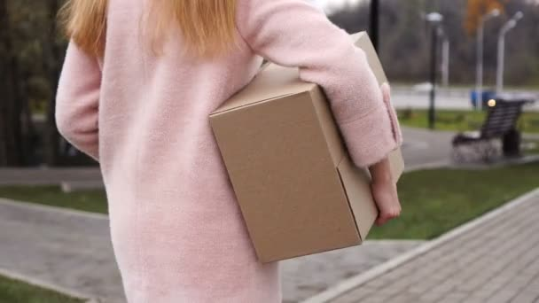 Unrecognizable woman carries cardboard box outdoor