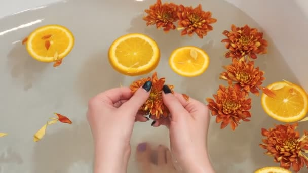 Woman taking a bath with flowers and oranges