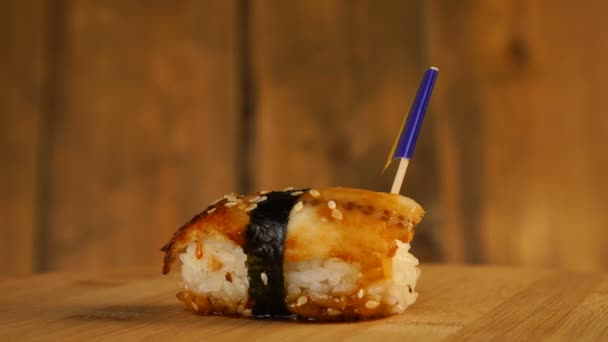 Sushi with fish, rice, seaweed and small flag of Romania on top rotate on a wooden turntable.