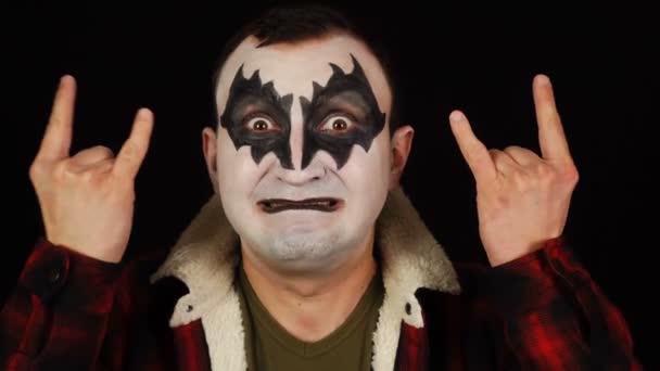 Férfi démon smink mutatja rock and roll jel, ördög szarv gesztus és keres őrült kifejezés