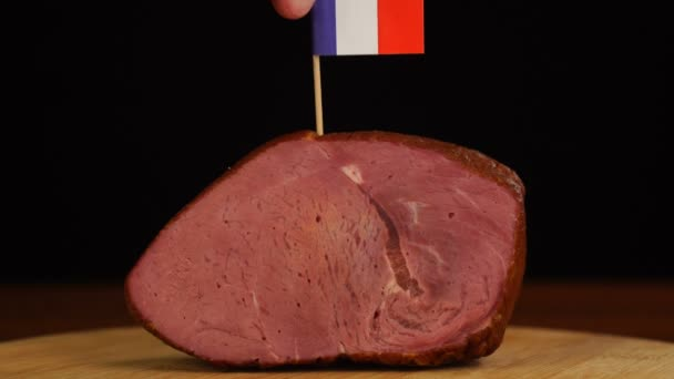 Person placing decorative French flag toothpicks into piece of red meat.