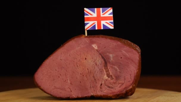 Person placing decorative Union Jack flag toothpicks into piece of red meat.