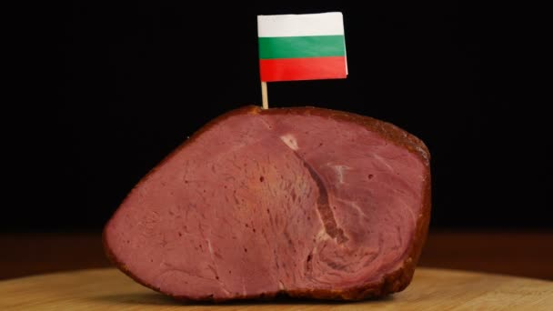 Person placing decorative Bulgarian flag toothpicks into piece of red meat.