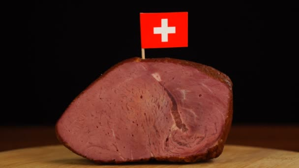 Person placing decorative Swiss flag toothpicks into piece of red meat.
