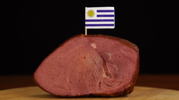 Person placing decorative Uruguayan flag toothpicks into piece of red meat.