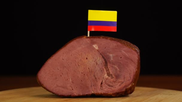 Person placing decorative Colombian flag toothpicks into piece of red meat.