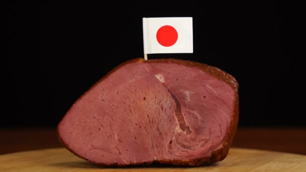 Person placing decorative Japanese flag toothpicks into piece of red meat.