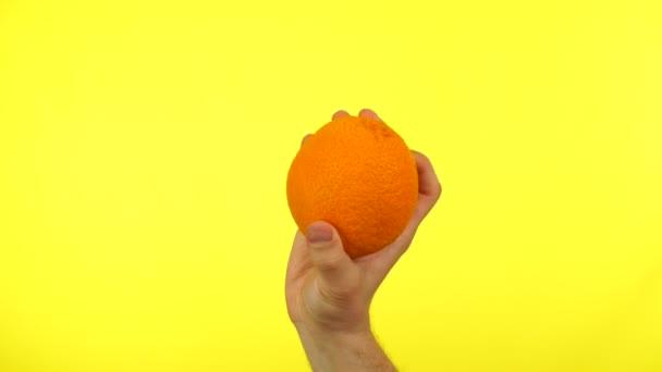 Man hand holding a fresh orange on yellow background