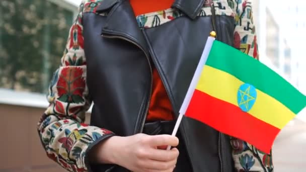 Unrecognizable woman holding Ethiopian flag. Girl walking down street with national flag of Ethiopia