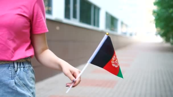 Unrecognizable woman holding Afghan flag. Girl walking down street with national flag of Afghanistan