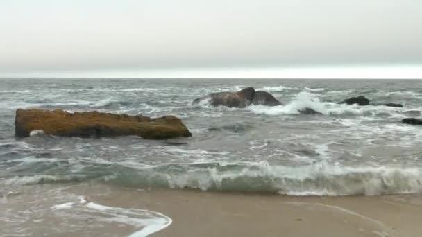 Sandy beach with choppy rough sea, yellow rocks, dense gray clouds covering sky.