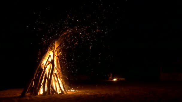 A huge bonfire on the sand and a small fire in the background  Lots of  sparks