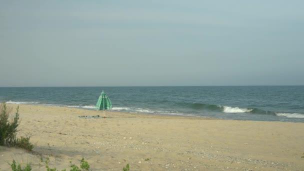 einsamer Sonnenschirm im Sand am Meer. Wind weht auf Regenschirm und Handtuch.