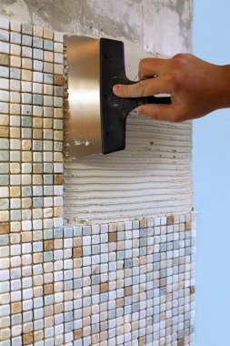 Repair in the apartment: installing the mosaic tile on the wall.