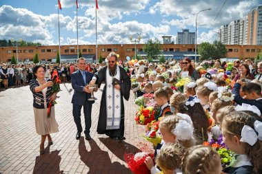 The priest sprinkles the crowd with holy water in city Balashikha, Russia.