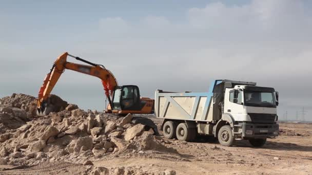 Excavator pours sand into a truck