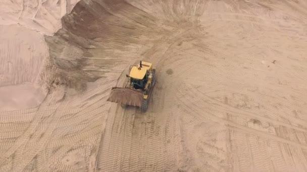 Luftaufnahme eines Bulldozers, der Sand in LKW gießt