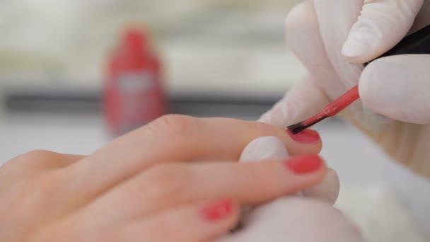 Nahaufnahme einer Kosmetikerin, die roten Lack aufträgt