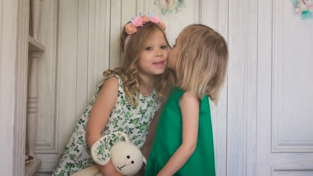 Two little pretty girls kissing each other indoors