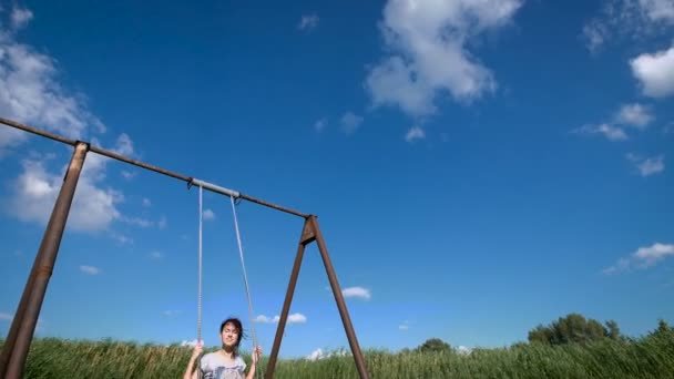 A young woman is swinging on a swing at a green field.