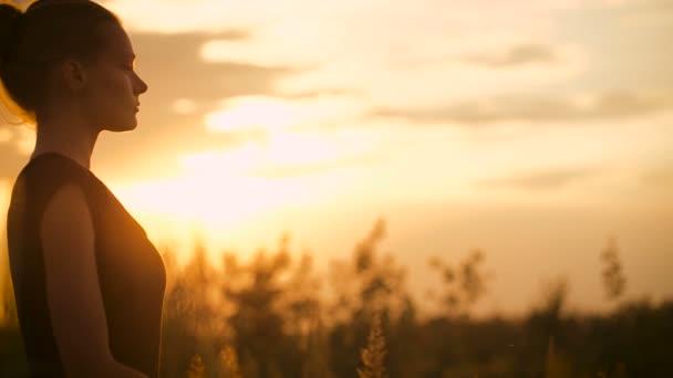 Krásná mladá zdravá žena dělá cvičení jógy při západu slunce