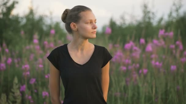 Beautiful young healthy woman standing at a green field and looking away