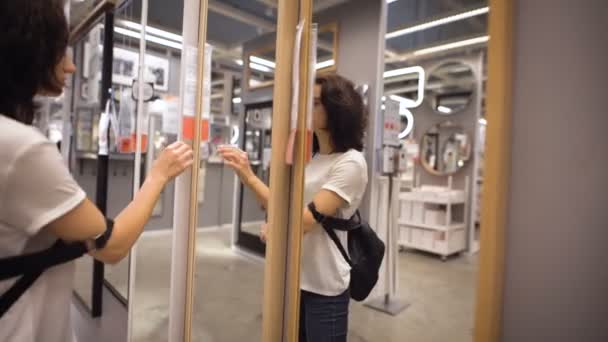 Csinos, fiatal nő választotta a ruhásszekrény a boltban