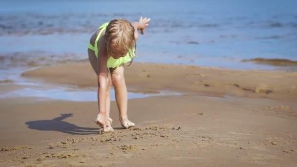 Cute little blonde girl having fun by a lake