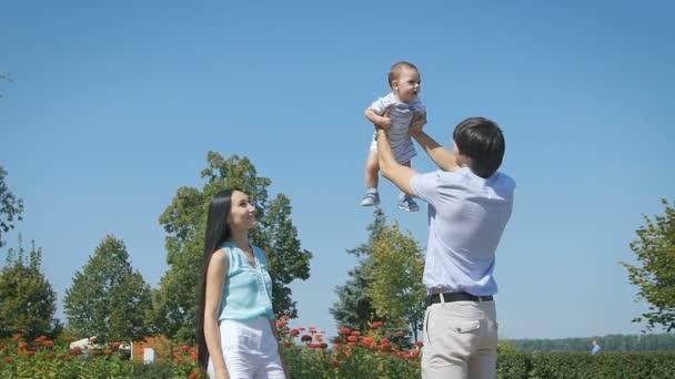 Šťastná rodina. Mladý otec hodí se dítě na obloze, na slunečný den