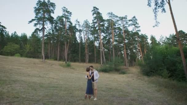 Krásný muž a žena, kteří se objímali na mýtině uprostřed borovicového lesa.