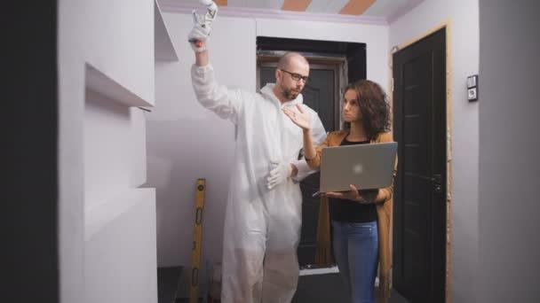 Mladé samice zákazník, vysvětluje práce na ukázkové snímky z Internetu, že se chce dostat pryč z opravy v bytě.