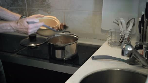 Opa bereitet Suppe für die ganze Familie zu.