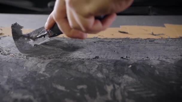 Eine Nahaufnahme einer Menschenhand mit einem Werkzeug. Ein Profi entfernt die Form mit Hilfe eines Zyklus aus dem Ton. Die Produktion