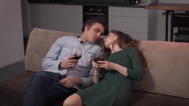 Pár milenců, co pijou víno. Muž svádí ženu v místnosti.