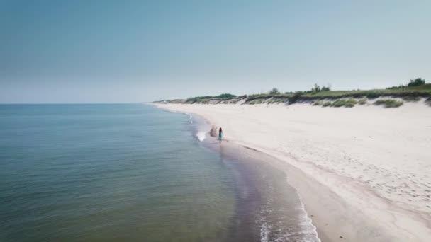 Luftaufnahme. Schöne Frau im blauen Kleid am Ufer der Ostsee.