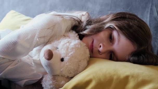 Aranyos lány lefekszik a macijával. .