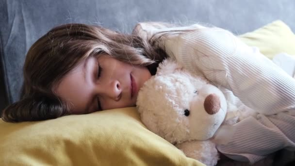 Dívka spí s medvídkem v ložnici doma.